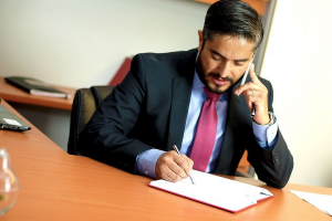 lawyer signing a paper while on a phone call