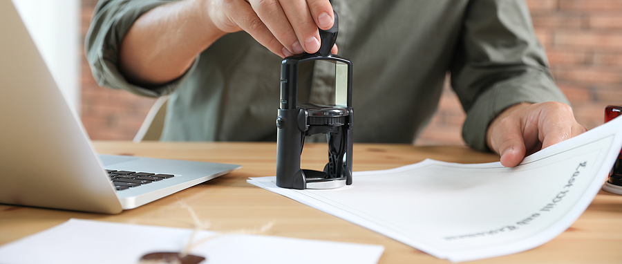Worker stamping document with self inking stamps